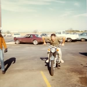 Bobby Gene McKinney on motorcycle in barracks parking lot.