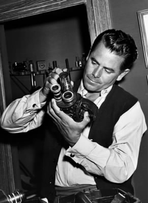 Glenn Ford checks his camera equipment.jpg