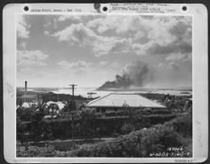 A view of Pearl Harbor with smoke from the Arizona rising in the air.